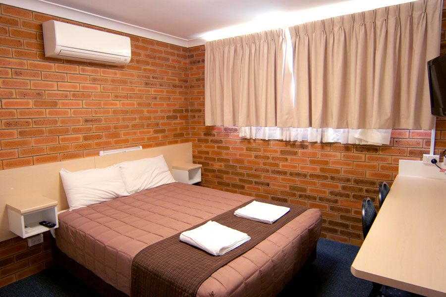 A room with brown queen bed, an air conditioner and curtains